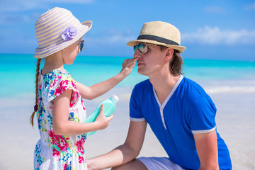 Little girl gets sun cream on her dad's nose