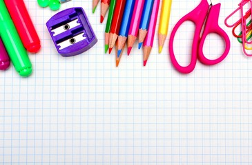 Colorful school supplies border over graphing paper