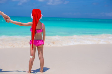 Back view of cute girl in red hat santa claus on the beach