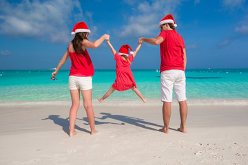 Happy family in Christmas Hats having fun on white beach