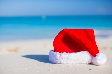 Closeup christmas hat on a white sandy beach