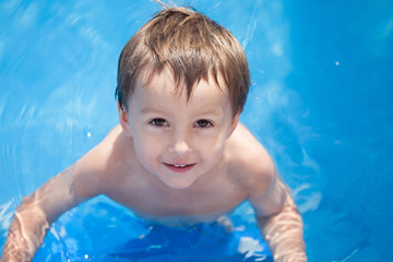 Cute boy in a pool, photographed from above