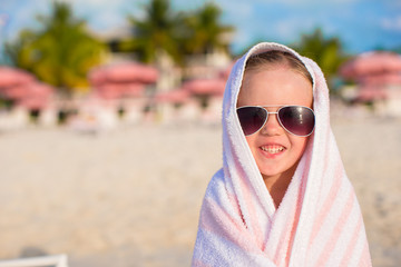 Portrait of little girl covered with towel at tropical beach