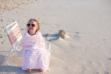 Adorable little girl in sunglasses covered with towel at