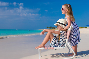 Little adorable girls in beach chair during caribbean vacation
