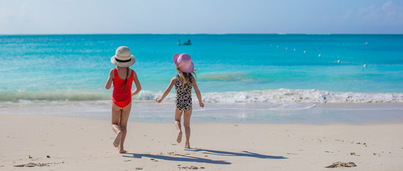 Back view of two happy little girls playing on white beach