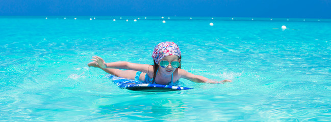 Adorable little girl in the sea on tropical beach vacation