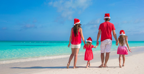 Back view young family of four in Santa Hat on tropical beach