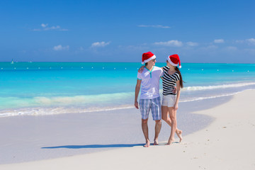 Young happy couple in red Santa hats on tropical sand beach