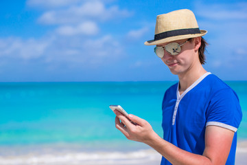 Young businessman with his phone on beach vacation