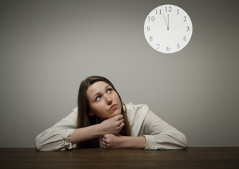 Girl in white and a clock showing several minutes to twelve.