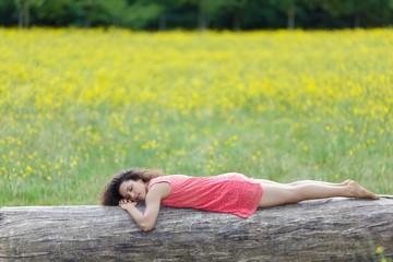 Beautiful young woman sleeping on a log