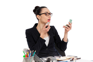 brunette businesswoman putting on her make-up at work