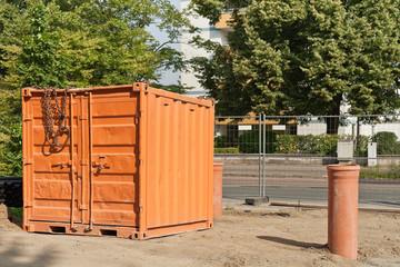 Ein oranger Werkzeugcontainer steht auf einer Strassenbaustelle