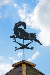 Weather vane on background of blue sky and clouds.