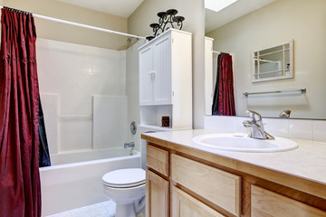 White bathroom interior with burgundy curtain