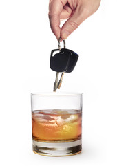 man hand holding car keys over whiskey glass on white background