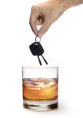 man hand holding car keys over glass of whiskey isolated on whit
