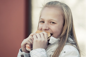 Teenage girl eating a burger
