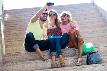 Three university students taking a selfie in the street.