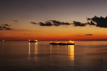 Cargo ship underway at sunset