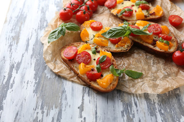 Tasty bruschetta with tomatoes , on old wooden table