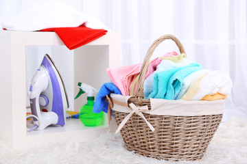Colorful towels in basket on home interior background