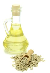A bottle of sunflower oil with seeds on white background