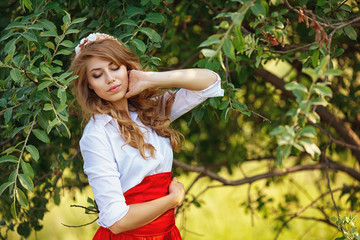 blonde curly woman standing under the tree