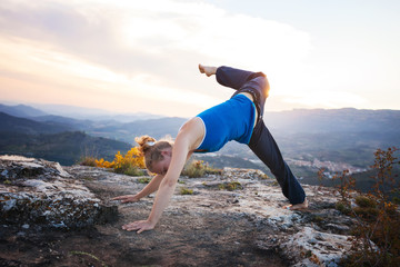 Young Caucasian woman working out on a rock against valley view