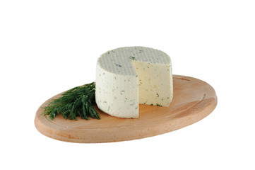 Cheese with dill on wooden cutting board