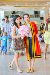 Graduate Thai college student standing with her friend