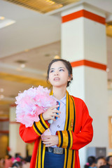 Thai college girl in academic gown is hoping in graduation