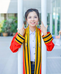 Graduate Thai college girl is holding poles happily