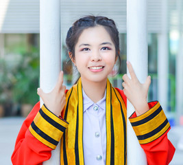 Graduate Thai college girl is is holding poles and smiling happi