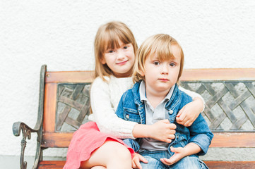 Portrait of adorable children sitting on a bench