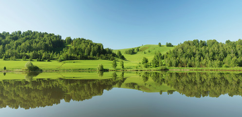 Beautiful summer panorama with green hills reflected in water
