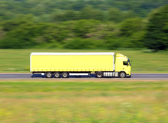 yellow truck driving on a road