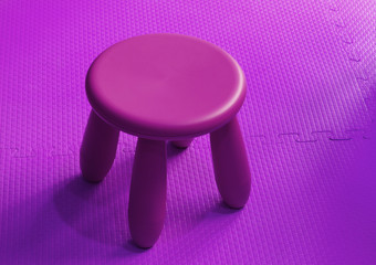 Small pink plastic stool for kids isolated on soft floor indoor