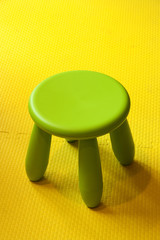 Small green plastic stool for kids isolated on yellow soft floor