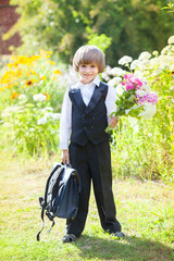 Schoolboy with a bouquet in the garden