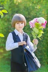 Boy in school uniform with a bouquet of flowers