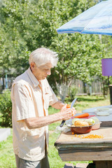 The elderly man cut vegetables for dinner in sunny day