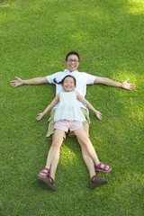 father and daughter lying on a meadow together