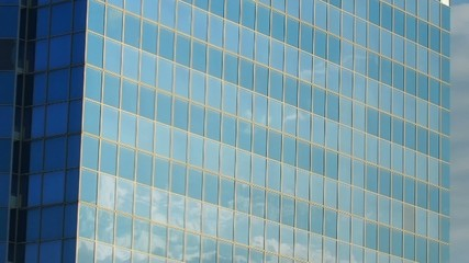 Moving clouds reflected in a glass wall of the building