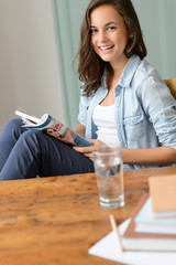Smiling teenage girl reading magazine at home