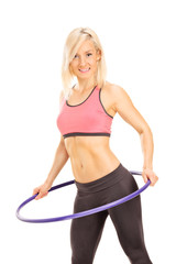 Young woman exercising with a hula hoop