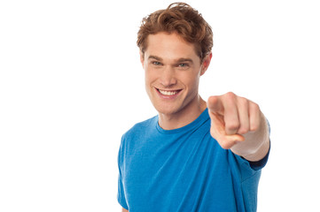 Cheerful man pointing towards camera