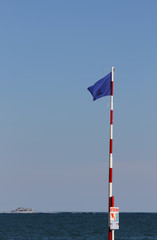 blue flag near the ocean