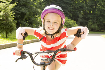 girl rides a bicycle in a park
